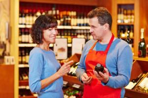 Verkäufer im Supermarkt empfiehlt einer lächelnden Frau eine Flasche Rotwein
